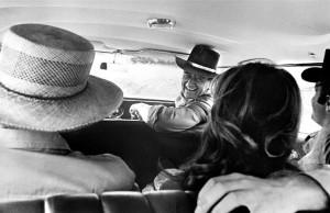 John Wayne in car with Howard Hawks, Michele Carey, and James Caan on the set of El Dorado (PRNewsFoto/John R. Hamilton Collection)