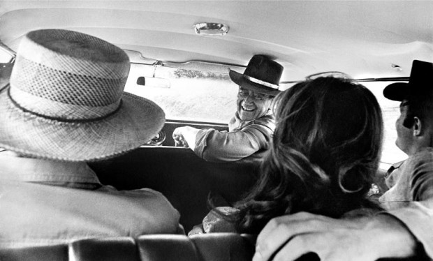 John Wayne in car with Howard Hawks, Michele Carey, and James Caan on the set of El Dorado (PRNewsFoto/John R. Hamilton Collection)